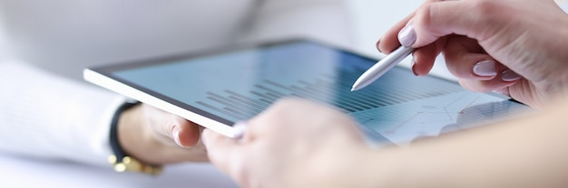 Женская рука держит стилус над включенным планшетом с бизнес-записями вместе с коллегой.