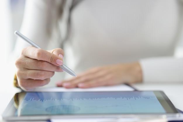 Женская рука держит стилус над включенным планшетом с бизнес-записями.