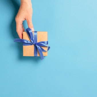 Female hand holds, takes, get a gift on a blue background.