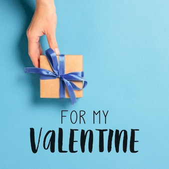 Female hand holds, takes, get a gift on a blue surface