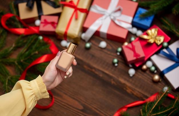 여성 손 크리스마스 선물 근처 톤 크림을 보유