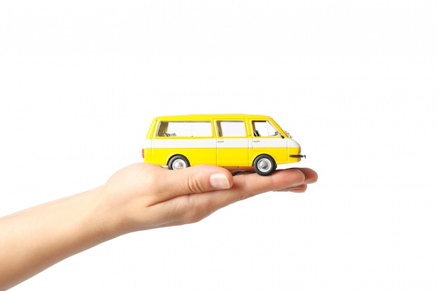 Female hand holds toy bus, isolated on white