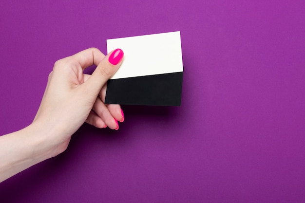 Female hand holds a two blank business card on a purple background.
