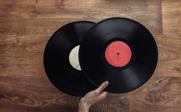 女性の手は木の床に2つのビニールレコードを持っています。
