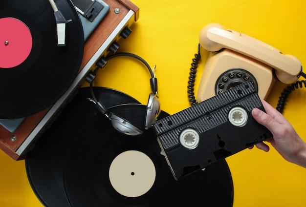 女性の手は、ビデオカセットを保持しています。 80年代スタイル。ビニールプレーヤー、ヘッドフォン、黄色の背景に回転式電話。トップビュー、フラットレイアウト