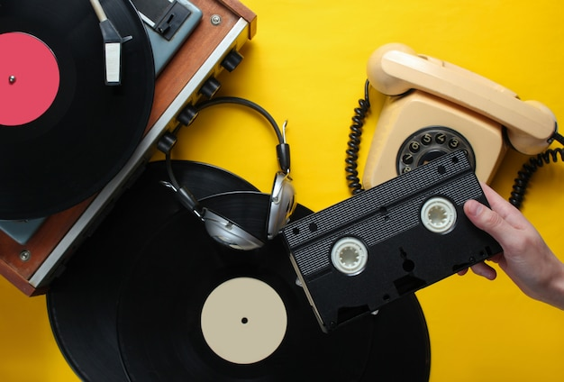 Female hand holds video cassette. 80s style. vinyl player, headphones, rotary phone on yellow background. top view, flat lay