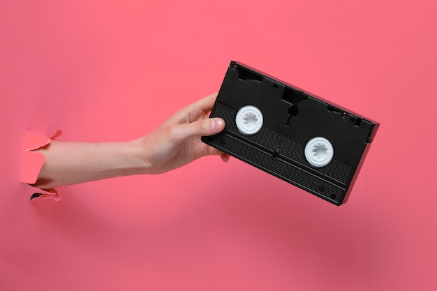 Женская рука держит видеокассету через разорванный фон розовой бумаги. минималистичная ретро-концепция
