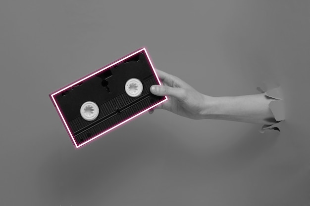 Female hand holds video cassette with neon frame through torn  paper