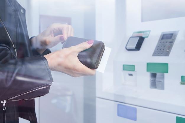 여성의 손은 atm 배경에서 지갑과 신용 카드를 들고, 현금을 인출하고, 금융 거래를 합니다.
