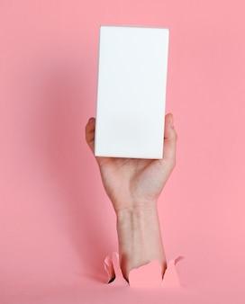 Женская рука держит белую коробку через разорванную розовую бумагу. минималистичная креативная концепция моды