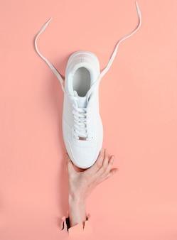 女性の手は、破れたピンクの紙を通して白いスニーカーを持っています。ミニマルなクリエイティブなファッションコンセプト