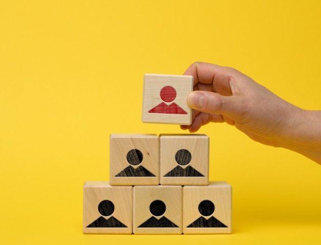 Female hand holds a wooden block on a blue background. recruitment concept, teamwork, effective management. ceo search, yellow background