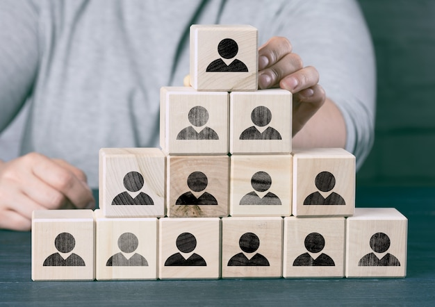 Female hand holds a wooden block on a blue background. recruitment concept, teamwork, effective management. ceo search