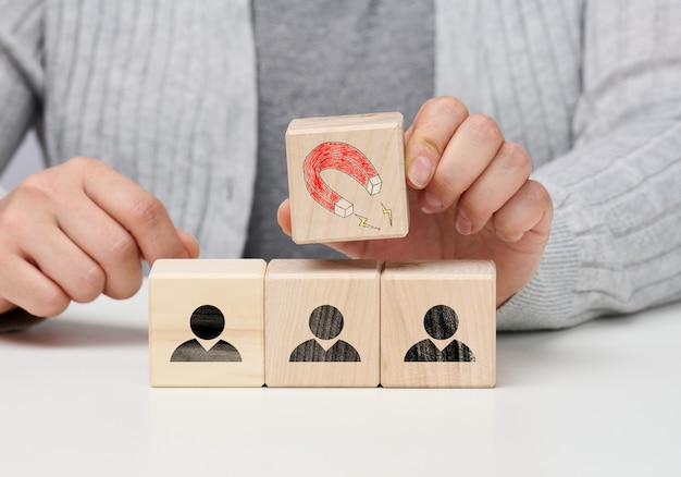 Female hand holds a wooden cube with a magnet over the cubes with little men, recruiting for a strong team. open vacancies in the company