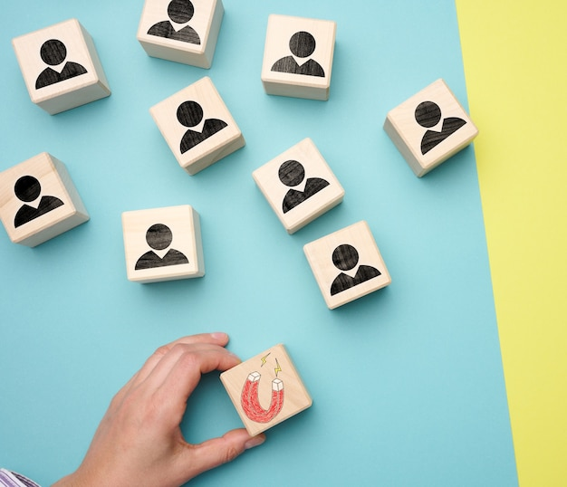Female hand holds a wooden cube with a magnet and wooden cubes with little men, recruiting for a strong team. open vacancies in the company, flat lay