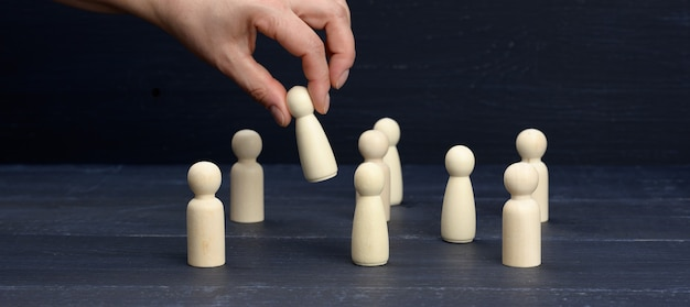 Female hand holds a wooden figurine above the crowd. the concept of finding employees, talented and unique employees. career growth, choice of a leader, banner