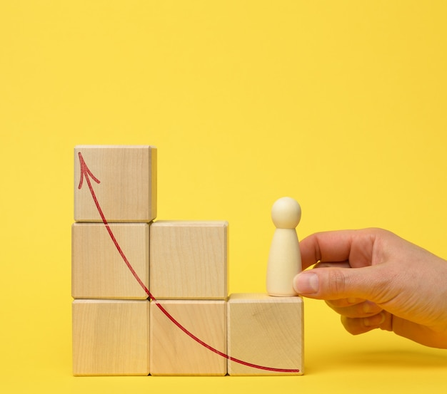 Female hand holds a wooden figurine on a ladder of cubes on a jelly surface. career growth concept, promotion, personal growth, coach help
