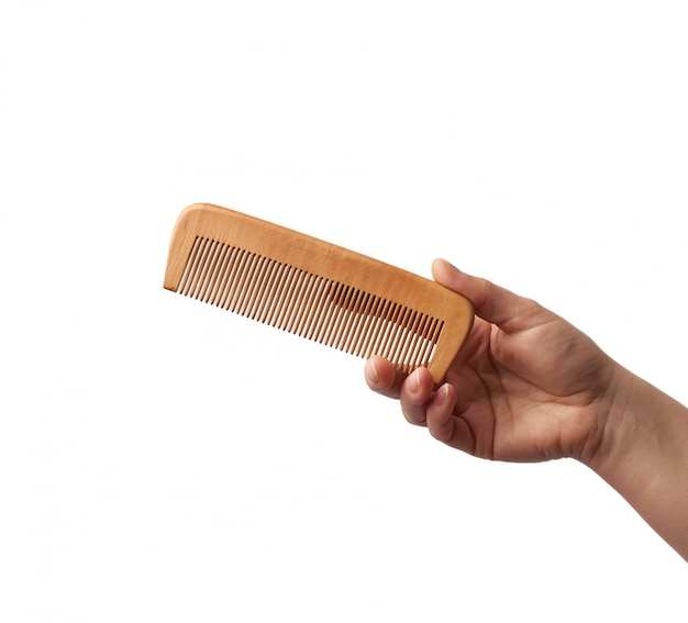 Female hand holds wooden hairbrush isolated on a white surface