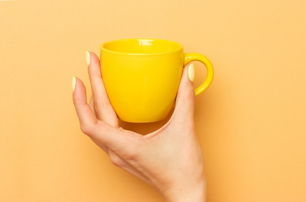 Female hand holds a yellow ceramic mug for coffee and other drinks