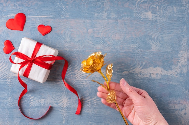 Female hand holds yellow gold rose and gift with red hearts on wooden grunge blue