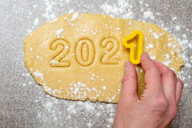 A female hand holds a yellow shape with the number one above the text to make the numbers from the text 2021