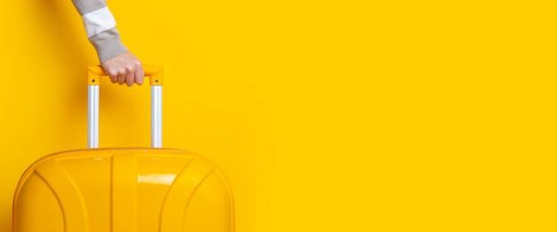 Female hand holds a yellow suitcase on a bright yellow background. banner.