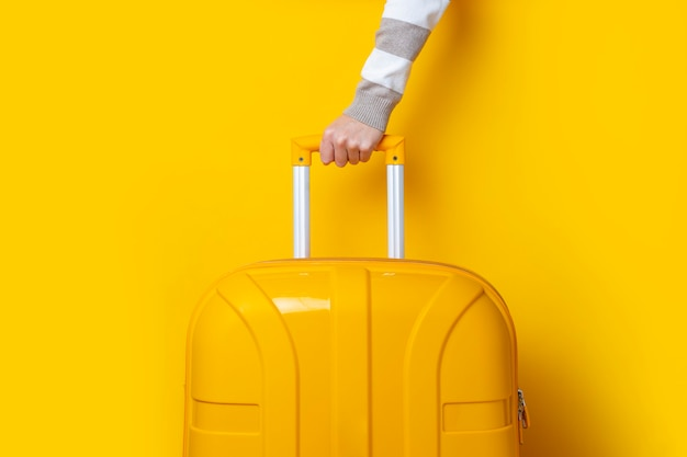 Female hand holds a yellow suitcase on a bright yellow background.