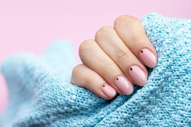 マニキュアと青いニットセーター生地の女性の手