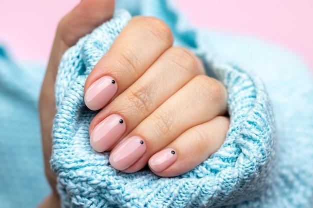 トレンディな美しいマニキュアと青いニットセーター生地の女性の手-ピンクの背景に黒い小さな点が付いたピンクのヌードネイル。セレクティブフォーカス。クローズアップビュー
