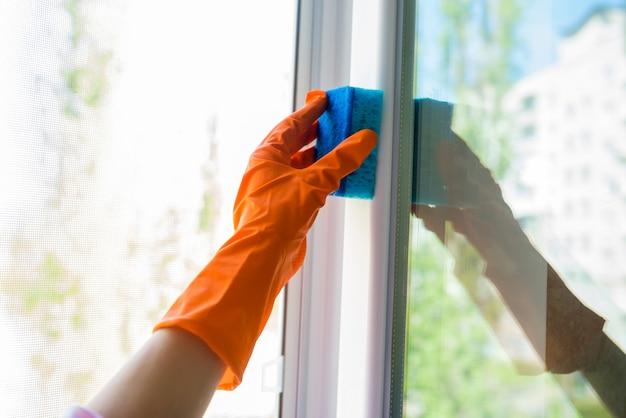 Женская рука в перчатке моет окно