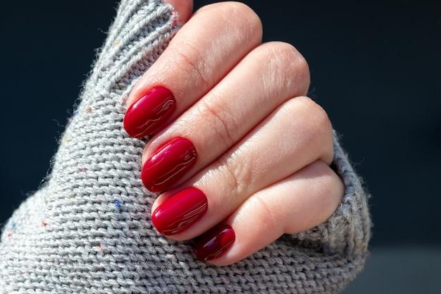 美しい光沢のあるマニキュアを備えたグレーのニットセーター生地の女性の手-バーガンディ、濃い赤色の爪。セレクティブフォーカス。クローズアップビュー