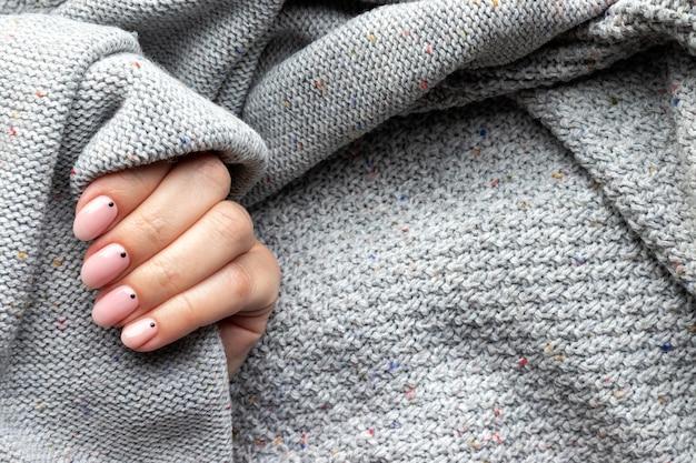 トレンディな美しいマニキュアとグレーのニットセーター生地の女性の手