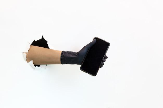 Женская рука в латексной черной перчатке в разорванном отверстии на белом фоне держит мобильный телефон. карантинные меры по предотвращению распространения covid 19. рука в перчатке через разорванную бумагу