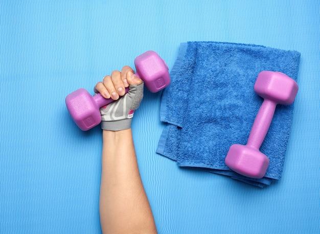 ピンクのスポーツグローブの女性の手は紫色の1キログラムのダンベルを保持しています