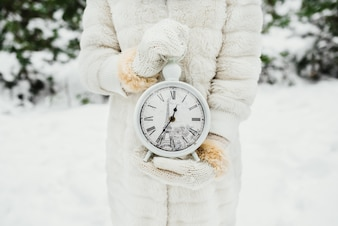 Female hand in a white knitted mittens holding big watches on winter background