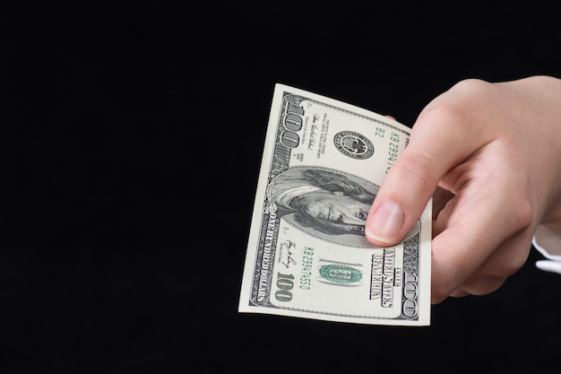 白いシャツを着た女性の手は、黒い背景で隔離、手に100ドル札を保持し、表示します