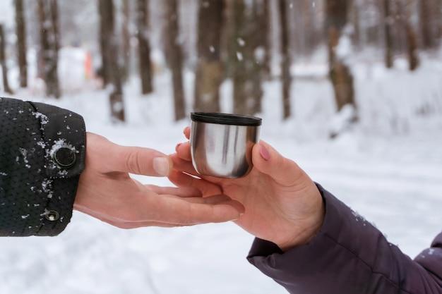 겨울 공원에 있는 여성 손이 친구에게 뜨거운 음료가 든 머그잔을 건네줍니다.
