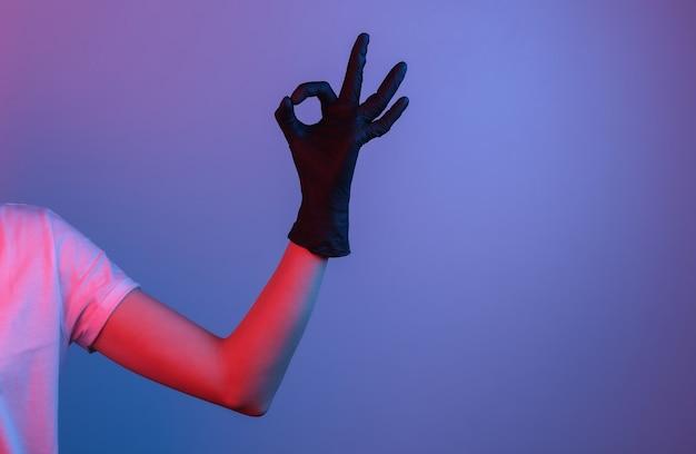 검은 라텍스 장갑에 여성의 손은 괜찮아 기호를 보여줍니다. 그라디언트 네온 불빛