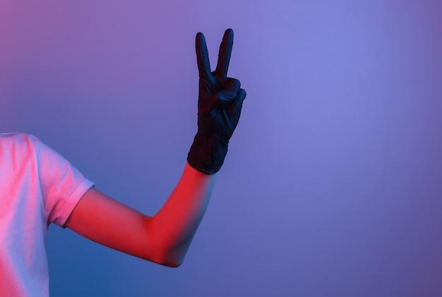 검은 라텍스 장갑에 여성의 손을 v 기호를 보여줍니다. 그라디언트 네온 불빛