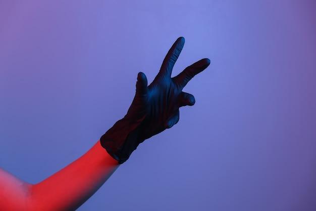 검은 라텍스 장갑에 여성 손입니다. 그라디언트 네온 불빛