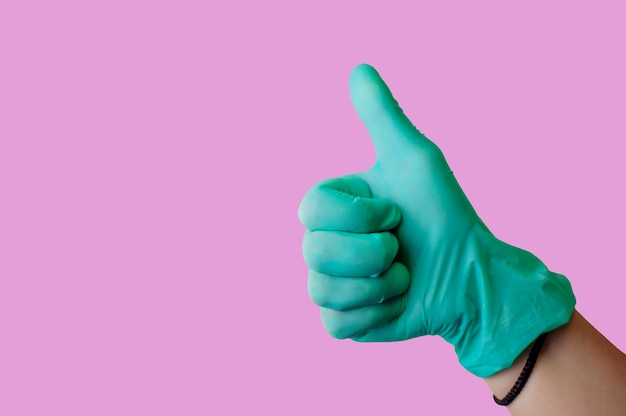 青いラテックス手袋の女性の手はジェスチャーのように親指を立てる