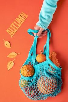 Женская рука в голубом мятном свитере держит тыквы в бирюзовом стринге на оранжевой бумаге