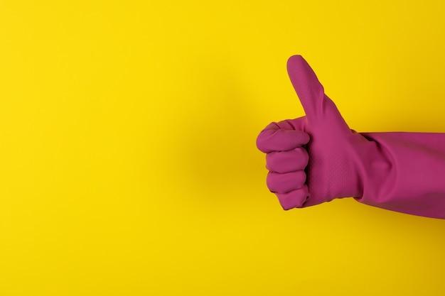 黄色の背景に家事手袋の女性の手