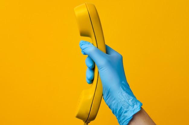 Женская рука в медицинской перчатке держит желтый телефонный динамик