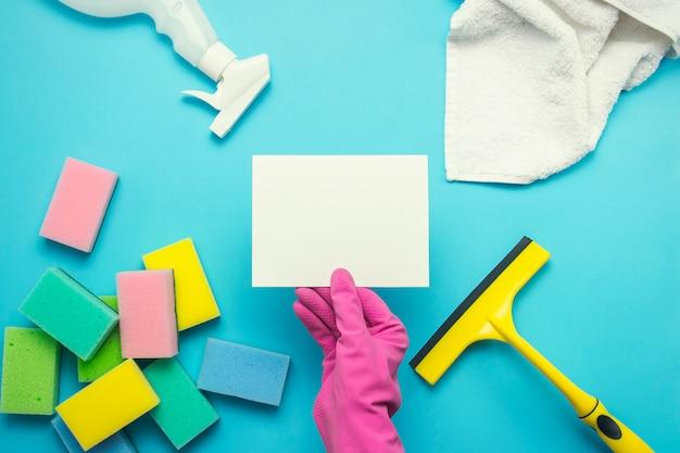 Женская рука в розовых перчатках держит пустую карточку и перчатки, спрей, губки, скребок для окон, полотенце на синем фоне. концепция уборки. копировать пространство плоская планировка, вид сверху