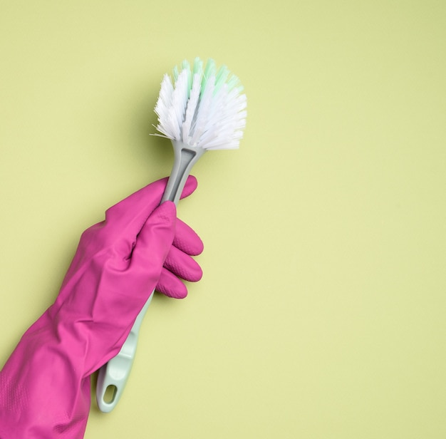 Женская рука в фиолетовых резиновых перчатках держит пластиковую щетку для чистки на зеленом фоне