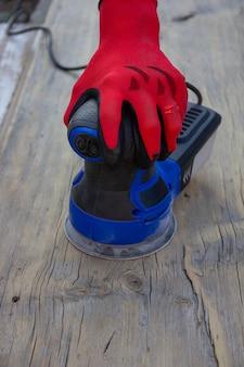 Женская рука в красной защитной перчатке шлифует старую серую доску электрической шлифовальной машинкой, вид спереди с копией пространства