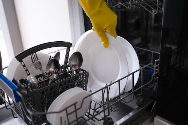 식기 세척기 근접 촬영에 더러운 접시를 넣어 고무 장갑에 여성 손