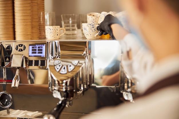 カフェのカップ加温トレイからカップを取るゴム手袋の女性の手