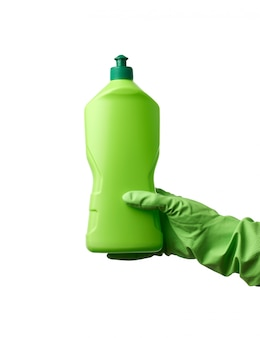 ゴム手袋の女性の手は、家庭で皿や物を洗うための洗剤が付いた緑色のプラスチックボトルを保持しています。